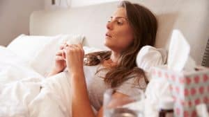Woman in bed with a cold and inflammation holding a tissue