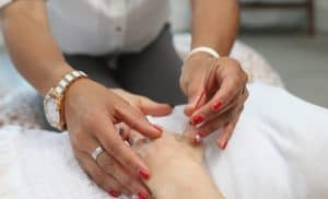 Woman's hands applying acupuncture needles to person's hand