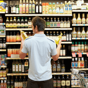 """Man looking for """"natural"""" cooking oils in a grocery store"""
