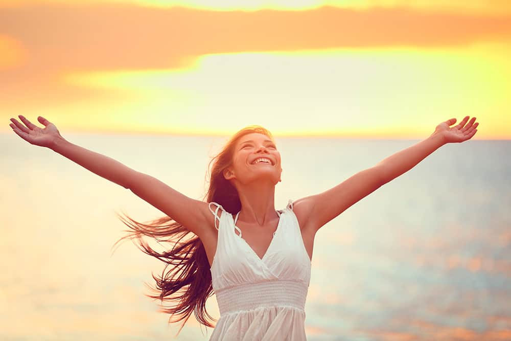 Free happy woman arms up praising freedom at beach sunset. Young adult enjoying breathing freely fresh air.